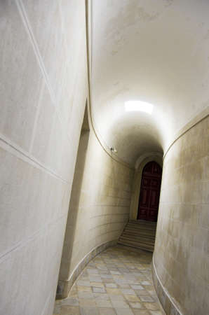 Long corridor with white walls and brown door inside of a building photo