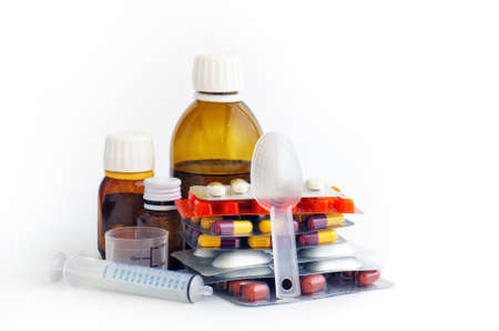 Assorted medical pills, capsules, tablets and syrup bottles over white background