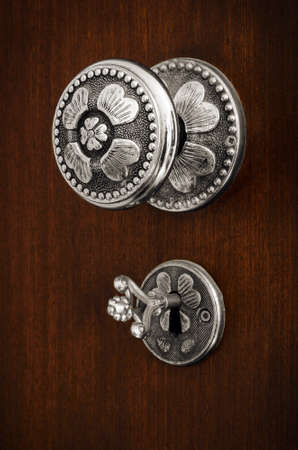 Old silver Doorknob and key on a brown wooden door photo