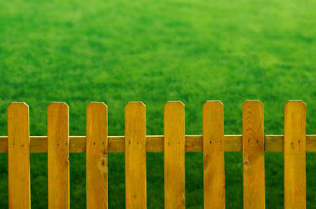 Yellow wooden fence over a green grass background photo