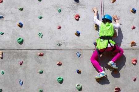 ni�o escalando: Joven de esfuerzo en la escalada de una pared para llegar a la cima Foto de archivo