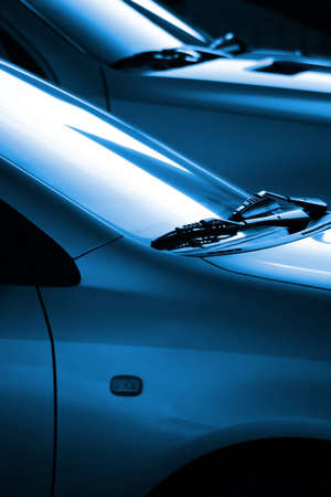 wiper: Black and blue image with the detail of two cars windshield wipers lit by low sunlight