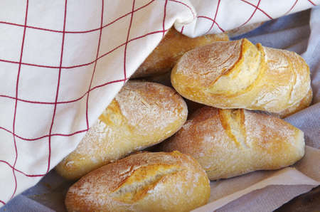 fresh crunchy baked buns and bread wrapped on tablecloth photo