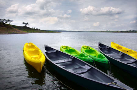 Green and yellow kayaks and canoes docked in the shore of a lake photo