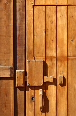 Detail of a closed wooden door with big wooden lock in an old shack  photo