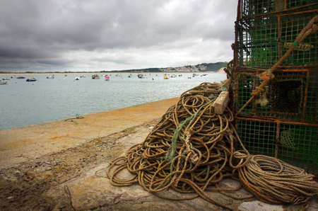 Stack of fishing traps and ropes in a pier and anchored boats on the sea photo