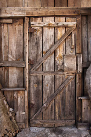 Detail of a closed wooden door with big wooden lock in an old shack
