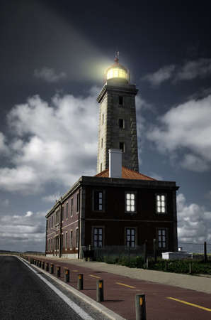 Closeup on a tall lighthouse with the lightbeam sweeping the dark sky of the night photo