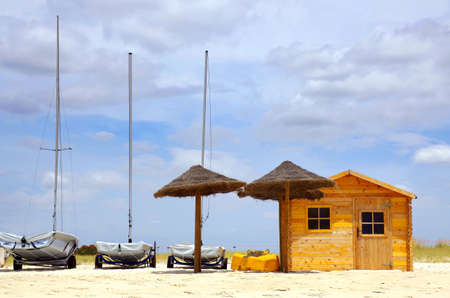sunshades: Three parked boats in the beach sand next to a wooden shack and sun-shades Stock Photo