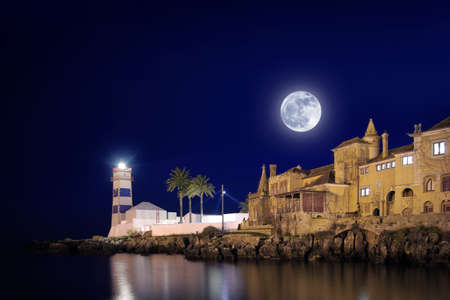 Lighthouse and house at night with full-moon in Cascais Portugal  photo