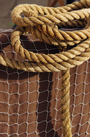 Detail of thick ropes and wide fishing net over a brown background photo