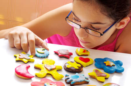 Young girl picking up one of many colorful and delicious cookies on a white table photo