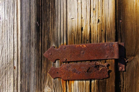 Detail of a closed wooden old door with big rusty iron hinge photo