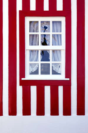 Single window on a red and white striped wall of a typical house in Costa-Nova, Aveiro, Portugal. photo