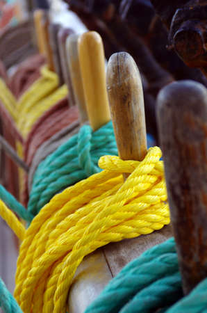 rigging: Colorful ropes wrapped around belaying pins in a sailing ship