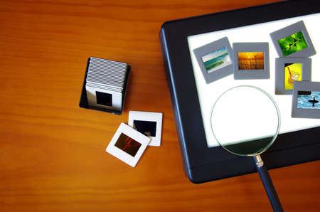 Top view of a lightbox with color slides and a magnifier lens over a wooden table photo
