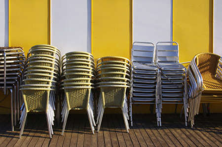 Groups of tables and chairs stacked and chained together against a yellow striped wall Stock Photo - 15253253