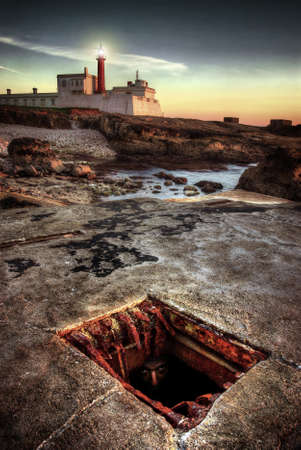 gouttière: Visage d'une personne cach�e sous terre furtivement dans le caniveau d'�gout � proximit� d'un phare dans la soir�e Banque d'images