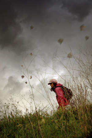 Young girl with hat and backpack walking alone in the countryside under bad weather photo