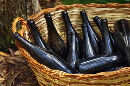 craft product: Straw basket full of dark and empty wine glass bottles