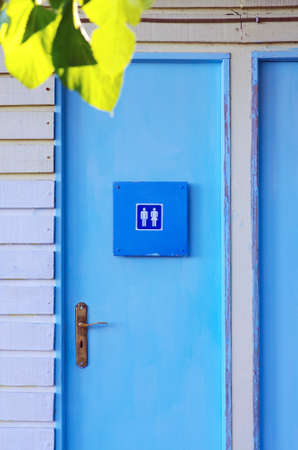 Blue painted wooden door of a unisex water-closet facility photo