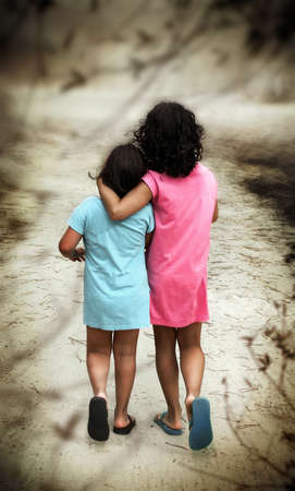 Two young girls in blue and pink dresses walking away with their backs turned photo
