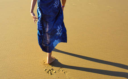 wet dress: Young girl with a blue dress walking barefoot in the beach