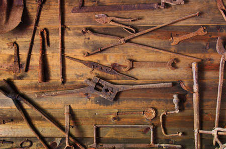 Wooden display with many old and rusty tools photo