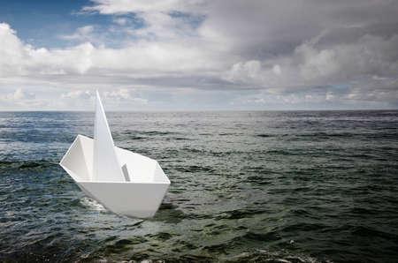 cloud drift: Single white paper boat adrift in the ocean under a stormy sky