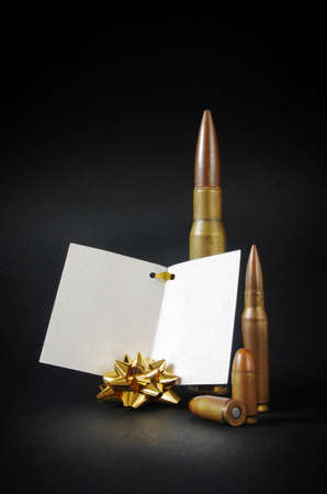 dedication: Composition with several gun bullets with a blank dedication card as an ironic gift Stock Photo