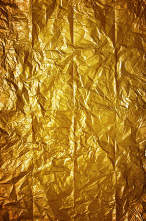 crinkled: Shining background of old wrinkled and folded yellow wrapping paper  Stock Photo