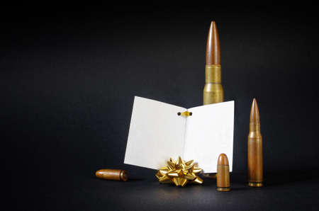 ironic: Composition with several gun bullets with a blank dedication card as an ironic gift Stock Photo