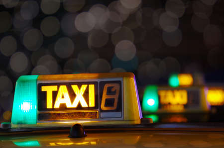 Row of taxi signs from parked taxis in a city street at night