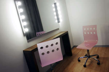 Makeup mirror with many light bulbs and two pink chairs photo