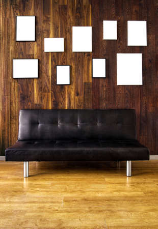 A black leather couch against a wooden covered wall with many empty picture frames photo