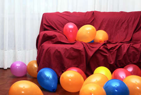 Many colorful party balloons laying in the floor and on a red couch in a living-room  photo