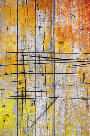 Background of cracked old wooden wall with orange and yellow paint peel photo