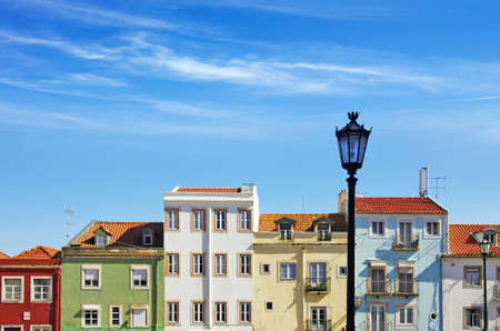 Picturesque Lisbon neighborhood with colorful block of houses under sunny blue sky