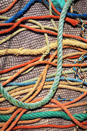 fishing nets: Messy background of colorful old fishing nets and ropes under sunlight Stock Photo