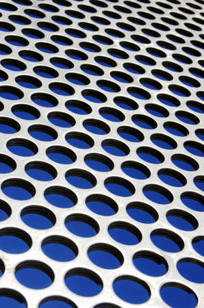 Aluminum perforated grid against a blue sky under sun light photo