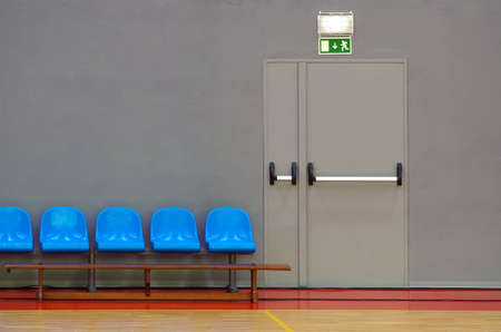 door handle: Emergency exit door next to a row of blue sits in a sports pavilion
