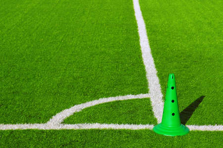 Detail of corner mark in a sports grass field with green plastic cone photo