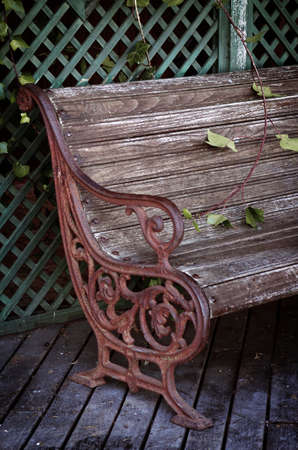 Vintage style garden chair with rusty forged iron parts and wooden slats photo
