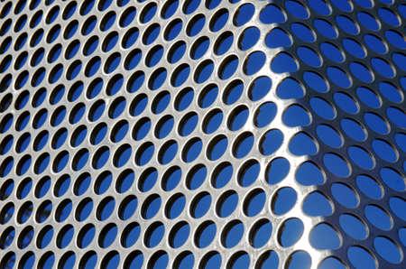 アルミ パンチング グリッド太陽光の下で青い空を背景 写真素材