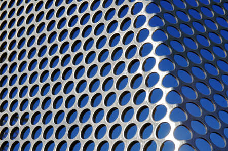 Aluminum perforated grid against a blue sky under sun light