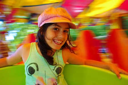 amusement: Little girl having fun in a carousel
