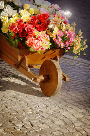 sundry: Wooden handcart with colorful artificial flowers over a stone sidewalk in a city street