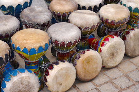 african drums: Many colorful congas or hand-drums for sale in a andicraft market