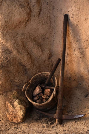 Ancient mining tools and basket full of rocks inside a tunnel in a mine