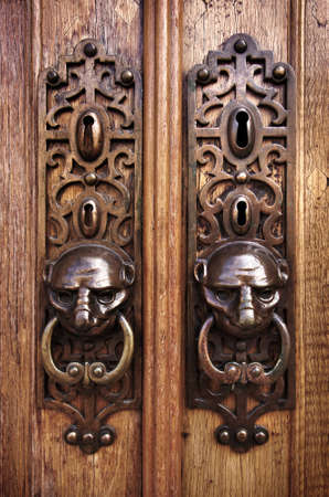 door lock: Two door knobs with knocking rings and animal heads in wooden doors Editorial